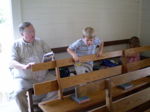 My dad and son Nathan sitting on one of the pews in the old Spring Ridge Baptist Church.